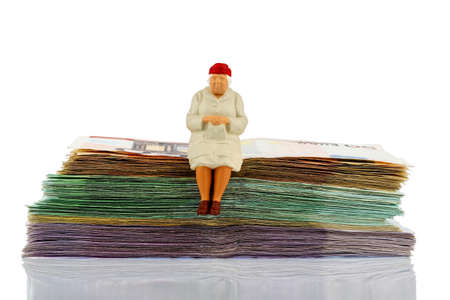 private insurance: figure of an old woman sitting on a stack of bills, symbolic photo for pension and retirement