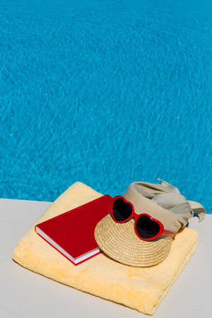 freetime: utensils for a nice and relaxing vacation day lying next to a swimming pool. relaxation on holiday. Stock Photo
