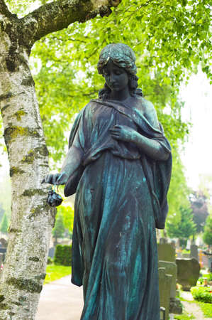 angel cemetery: an angel watches as a statue on the tomb in a cemetery Stock Photo