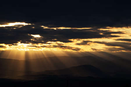 transcendence: sun rays breaking through the clouds over a mountain landscape