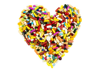 pharmaceutical drug: colorful tablets arranged in heart shape, symbol photo for heart disease, medication and pharmaceuticals
