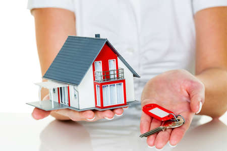 a broker for real estate with a house and a key. successful leasing and property for sale by real estate agents. photo