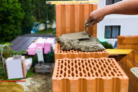 single familiy: anonymous construction worker on a construction site building a house built a wall of bricks. brick wall of a solid house. icon image for undeclared work and bungling
