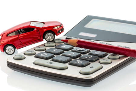 a car and a red pen is on a calculator. cost of gasoline, wear and insurance. car costs are not paid by commuter tax. Stock Photo