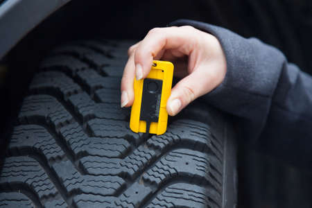 depth measurement: a young woman is measuring the tread depth of her car tire. the correct depth in the tread of a tire can prevent accidents. Stock Photo