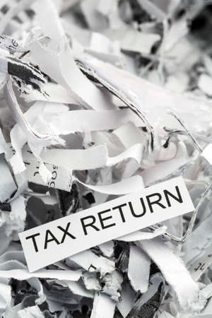 tax law: shredded paper tagged with tax return, symbol photo for data destruction, data protection and tax law Stock Photo