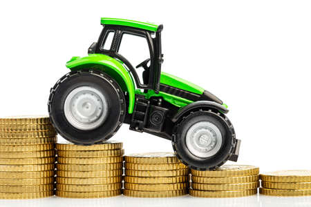 reckon: farmers in agriculture have to reckon with rising costs. higher preies in fodder, fertilizer and plants. tractor with coins