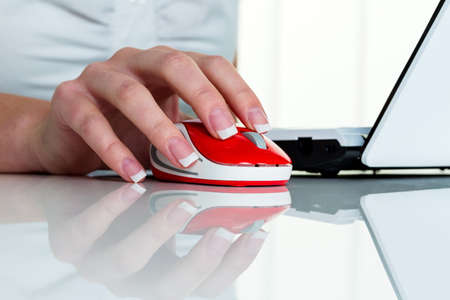 a woman working in an office and h�t the mouse of a computer in your hand. photo