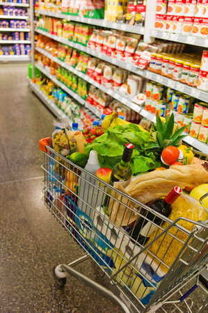 local supply: a shopping cart is standing in a aisle of a supermarket between the shelves.
