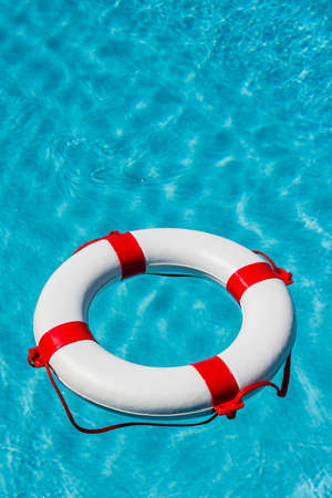 a rescue tire floating in a swimming pool. symbolic photo for rescue and crisis management in the financial crisis and banking crisis. Stock Photo