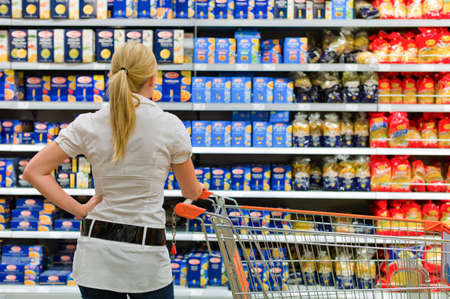 local supply: a woman is overwhelmed by the large selection in a supermarket when shopping.