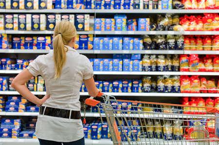 een vrouw wordt overweldigd door de grote keuze in de supermarkt bij het winkelen.