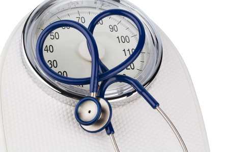 stethoscope and balance, symbol photo for weight, diet and heart disease photo