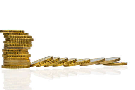slump: stacked coins and lying, symbol photo for debt, drop in profits and deductions Stock Photo