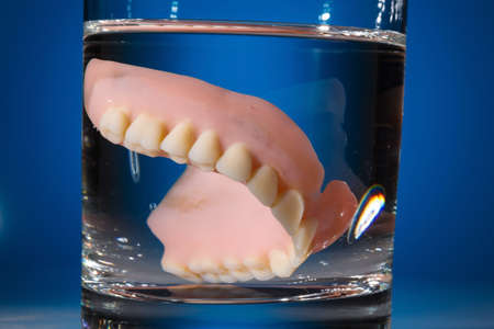 denture: a denture is cleaned in a glass with water. proper hygiene. Stock Photo