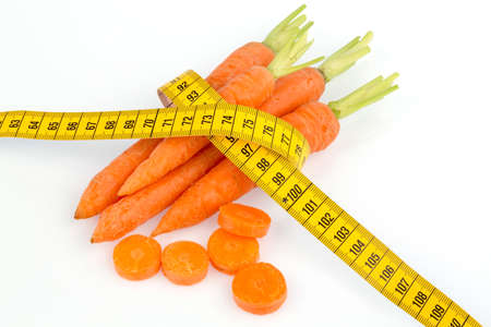 thinness: organically grown carrots with tape measure. fresh fruit and vegetables are always healthy. symbolic photo for a healthy diet. Stock Photo