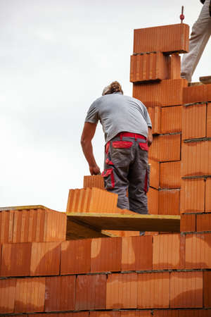 substantiate: anonymous construction worker on a construction site building a house built a wall of bricks. brick wall of a solid house. icon image for undeclared work and bungling