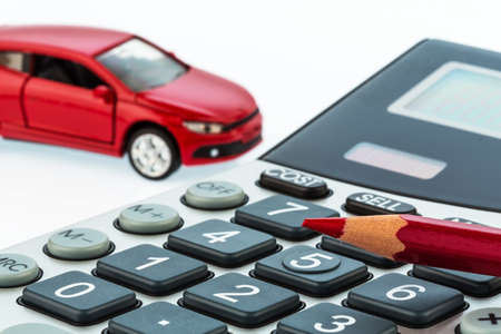 a car and a red pen is on a calculator. cost of gasoline, wear and insurance. car costs are not paid by commuter tax. Standard-Bild