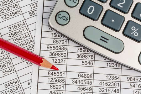 examiner: a calculator is on a balance sheet figures are statistics. photo icon for sales, profit and cost.