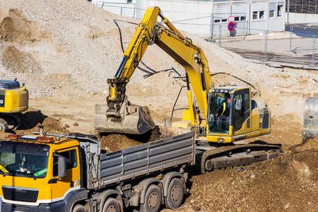 earthwork: excavator on a construction site. excavator bucket with soil, ground work. Stock Photo