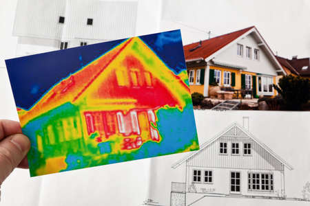 insulating: saving energy through thermal insulation. house with thermal imaging camera photographed. Stock Photo