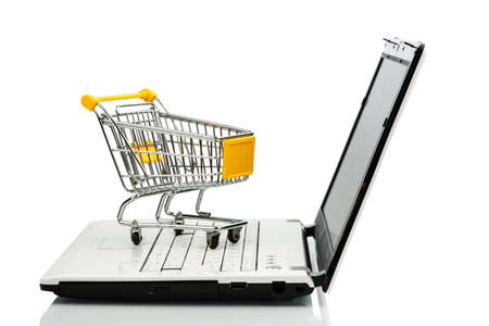 consumerist: shopping cart is on the keyboard of a laptop, symbol photo for online shopping and consumer behavior