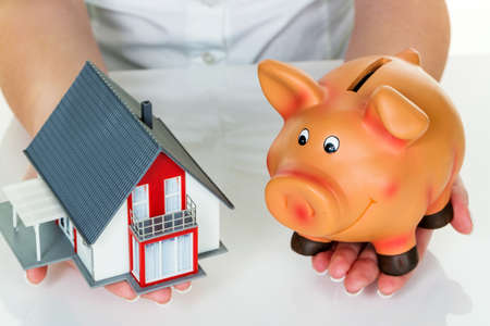 home purchase: a woman with a house and a piggy bank. the right financing for the home purchase.