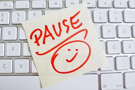 Ein Notizzettel ist auf der Tastatur eines Computers als Erinnerung: Pause