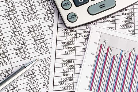 une calculatrice est sur un bilan chiffres sont des statistiques. photo icône pour les ventes, les bénéfices et les coûts.