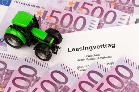 the lease agreement for a new tractor. with euro money and pen photo