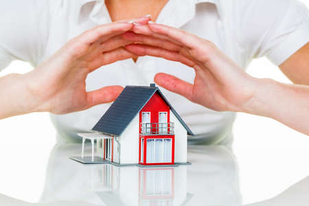 incendio casa: una mujer protege su casa y el hogar. un buen seguro y de buena reputación en calma financiación.