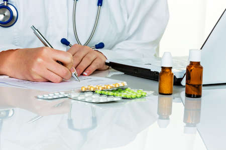 physicans: a young doctor prescribes medication. prescription pills are prescribed by the doctor. Stock Photo