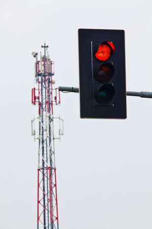 a mobile phone transmitter mast and red traffic lights. stop for network expansion.