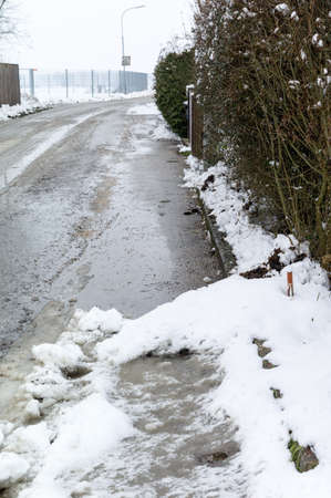 landowners: snow on sidewalk and street, symbol for accident risk  Stock Photo
