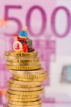 nursing allowance: woman in wheelchair on money stack, symbol photo for disability care allowance and costs in public health Stock Photo