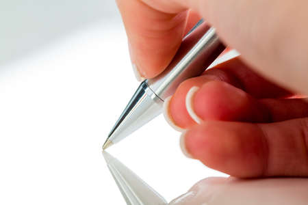 legacy: a hand with a fountain pen in the untrerschrift under a contract or testament.