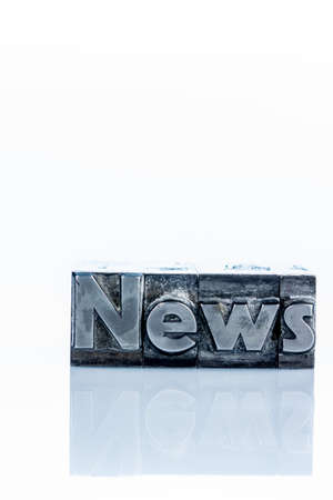 the word news written with lead letters. photo