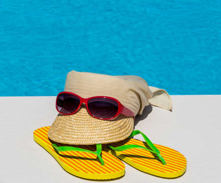 utensils for a nice and relaxing vacation day lying next to a swimming pool. relaxation on holiday. Stock Photo