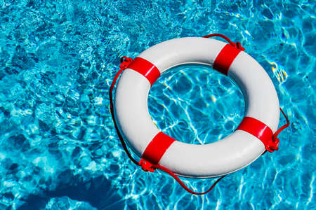 budget crisis: an emergency tire floating in a swimming pool.