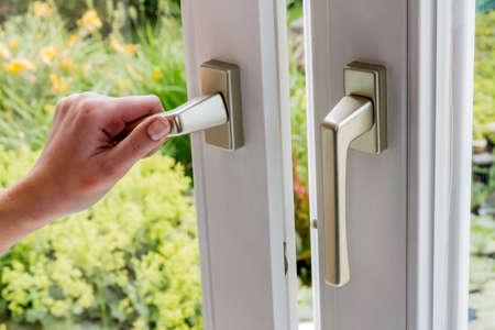 eine Frau öffnet ein Fenster in die Wohnung zu lüften. frische Luft in den Raum