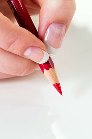 deletion: a hand holding a red pen. symbol photo for savings and budegt cuts. Stock Photo