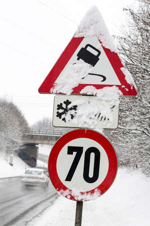 traffic signs and snow, symbol photo for winter weather, accident risk and speed limit Stock Photo
