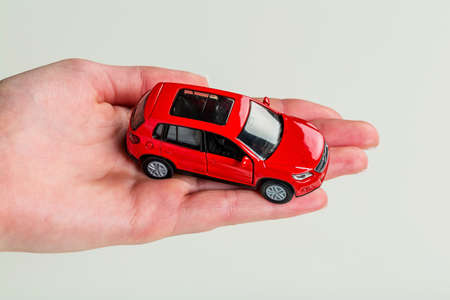 a hand holding the model of a car. symbol photo for car purchase photo