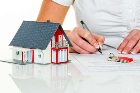 una mujer firma un contrato de compra de una casa en un agente de bienes raíces. Foto de archivo
