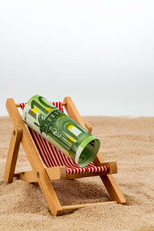 a deck chair with a euro banknote. symbol photo for saving on holiday and when traveling photo