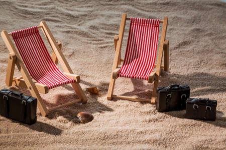 kkleine deck chairs on the sandy beach with suitcase photo