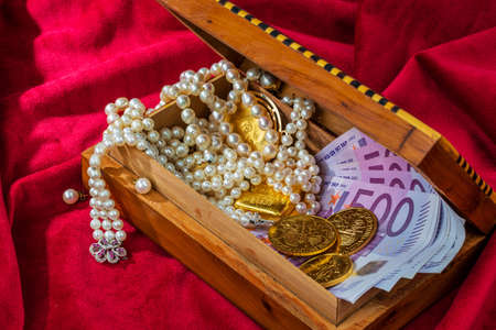 inheritance: gold coins and bars with decorations on red velvet. symbol photo of wealth, luxury, wealth tax.
