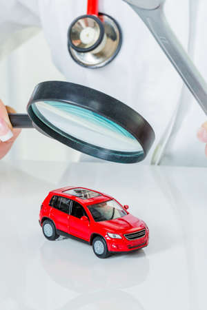 a model of a car is examined by a doctor. symbol photo workshop, service and car buying.