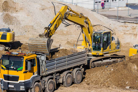 contruction: excavator on a construction site. bucket with soil, ground work.