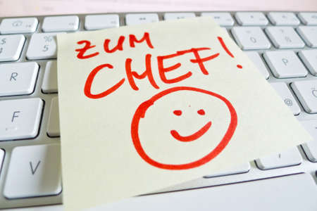 a sticky note is on the keyboard of a computer as a reminder: for chief Stock Photo